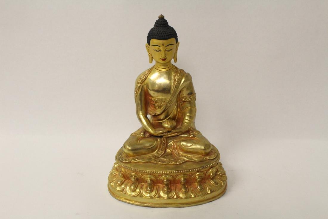 A gilt bronze sculpture of seated Buddha