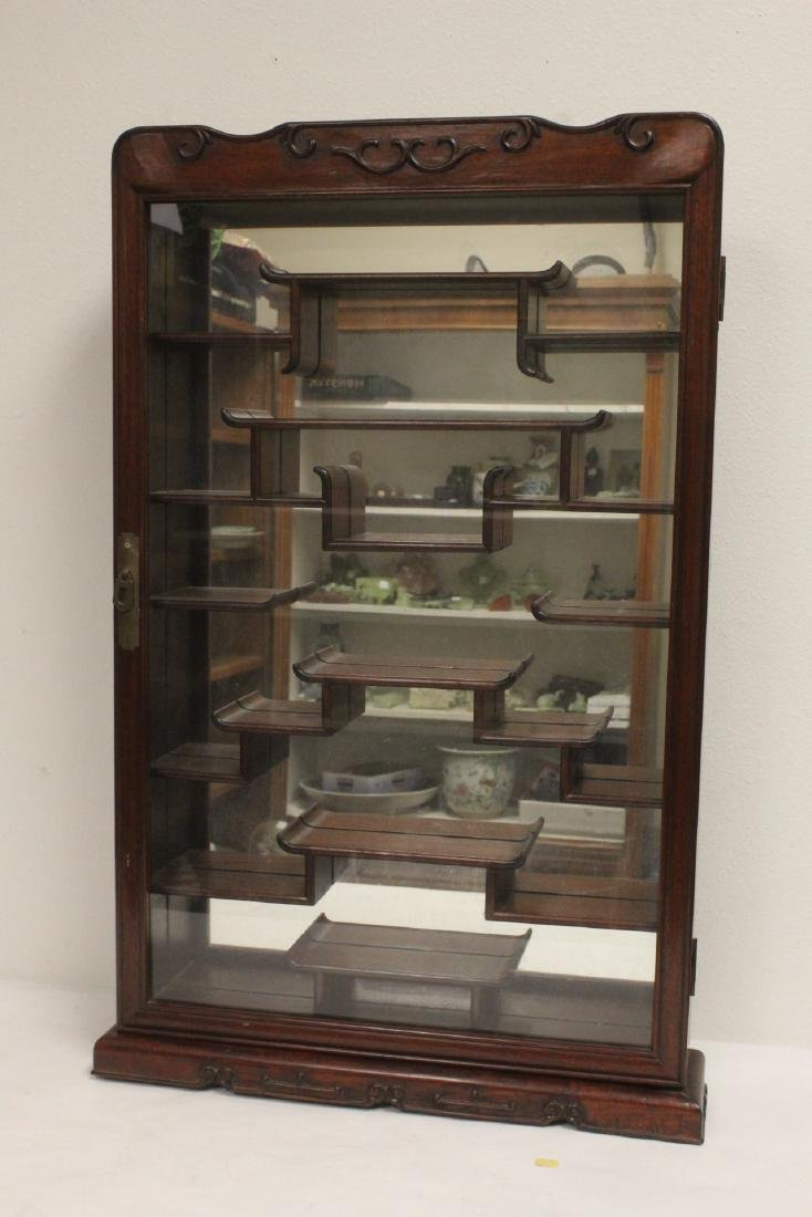 A rosewood wall hanging curio cabinet