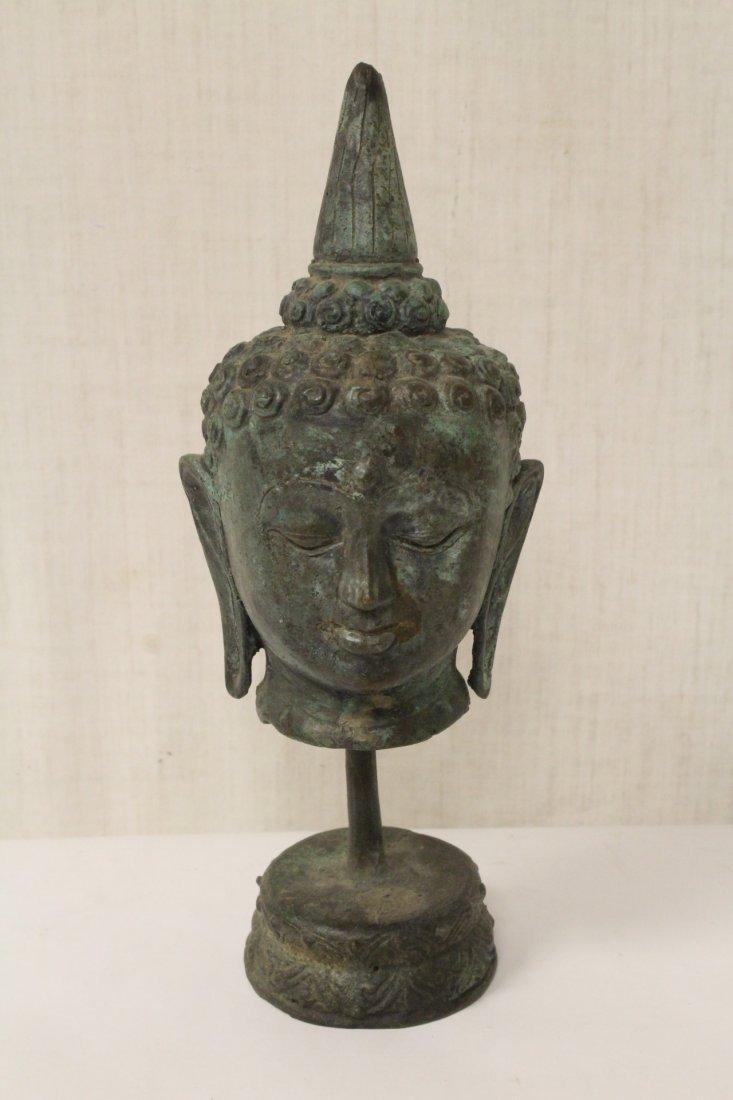 Bronze Buddha head on post
