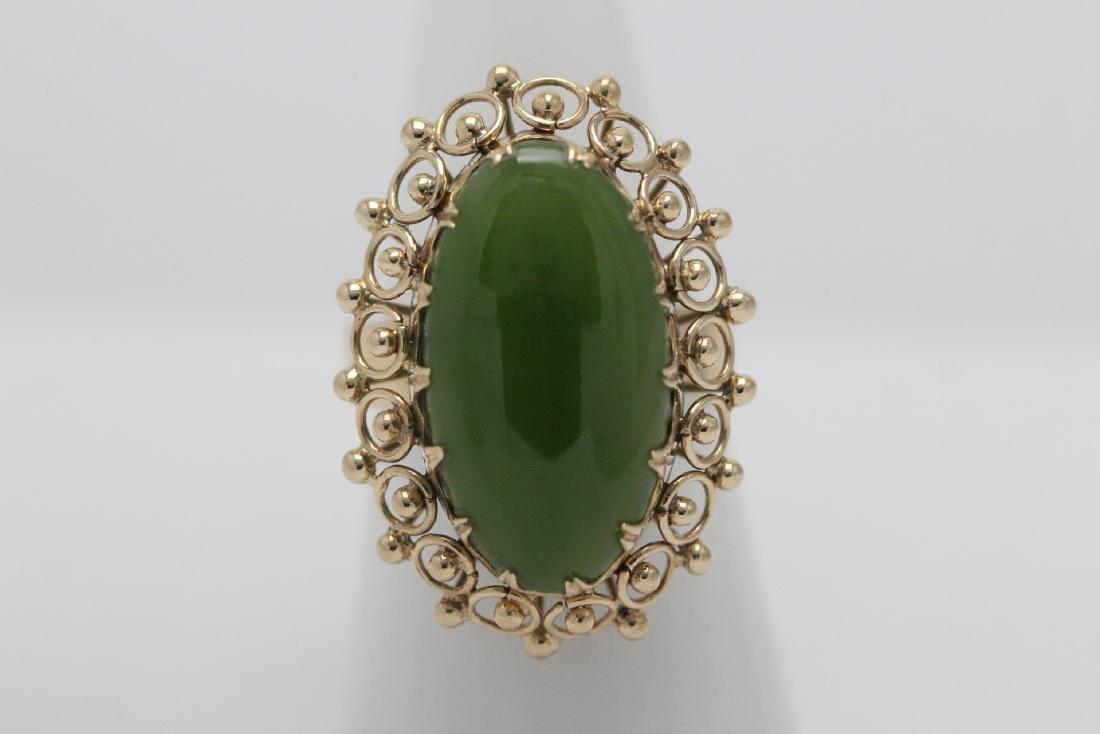An ornate 14K Y/G jadeite ring