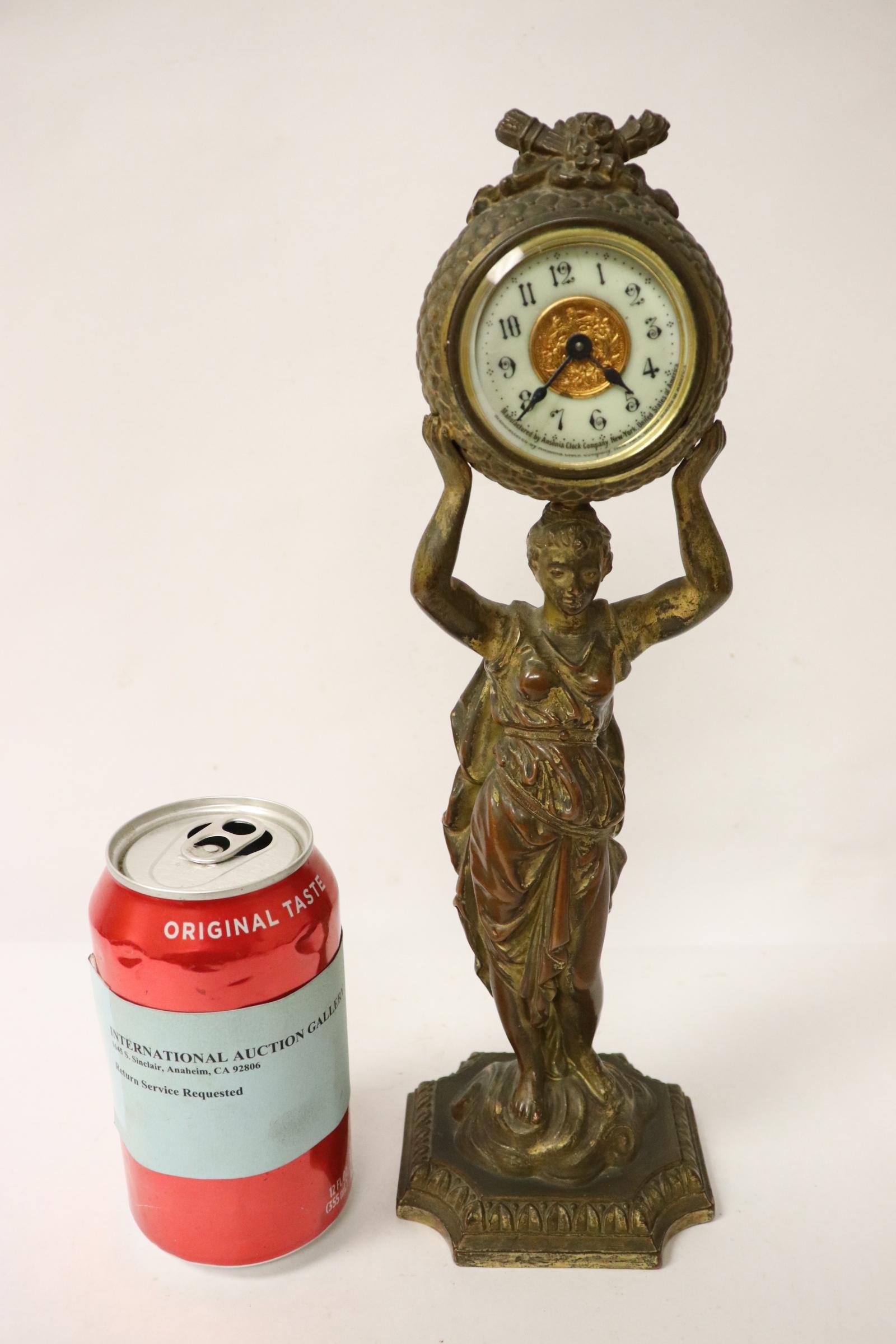 Gilt metal table clock with figure motif base