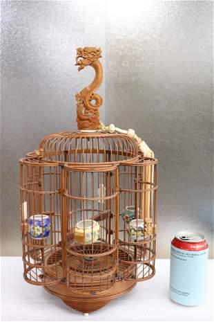 A bamboo bird cage with porcelain bird feeders