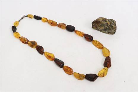 An amber bead necklace and a rough amber stone