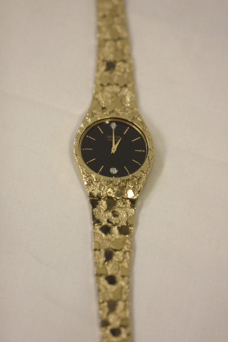 122: Man's Geneve wrist watch attached to a 10K Y/G ban