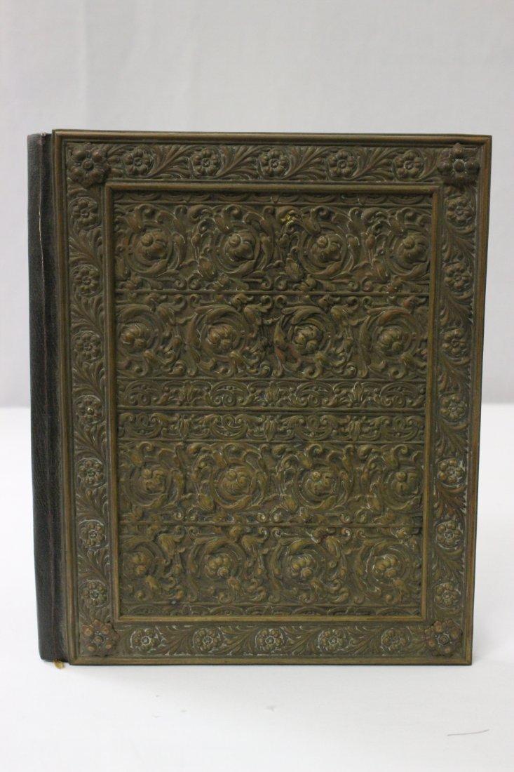 Antique book cover with repose copper plaque