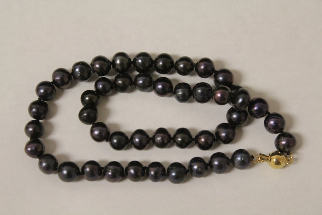 A black pearl necklace with 14K clasp