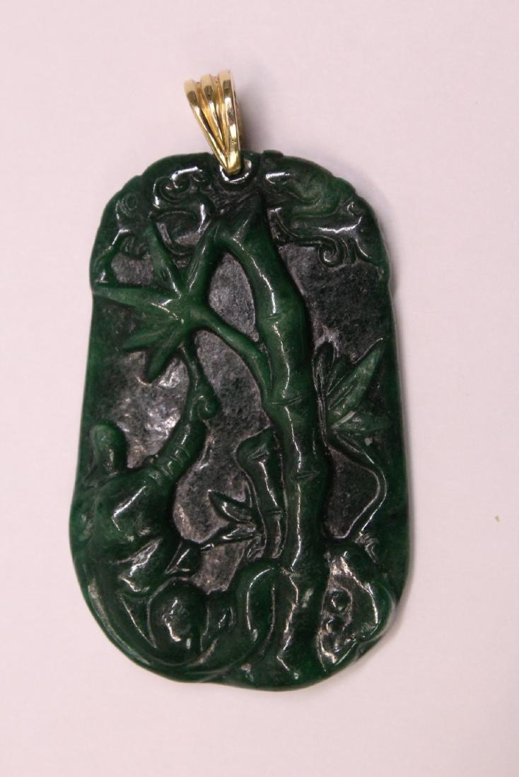 An emerald green jadeite pendant w/ 14K clasp