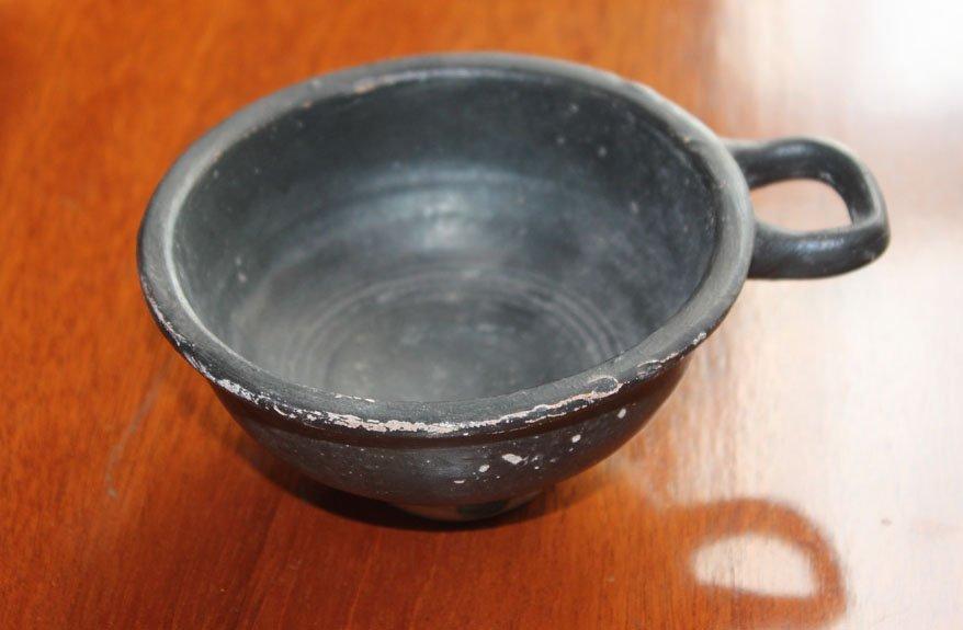 22: A black glazed red-ware wine cup, Greek, circa 400B