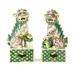 A pair of famille-vert biscuit figures of Dogs of Fo, C