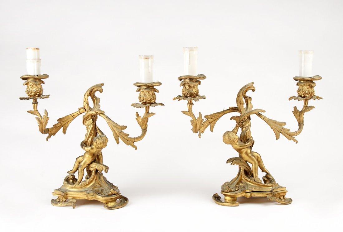 A pair of gilt bronze cherub and foliate form twin