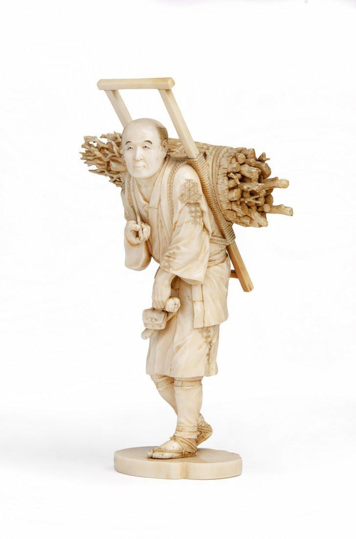 A Japanese ivory Okimono figure of a wood gatherer,
