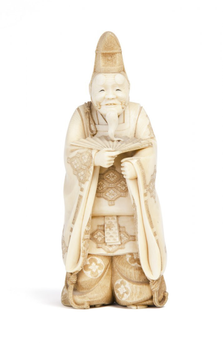 A Japanese ivory Okimono of an actor wearing a mask,