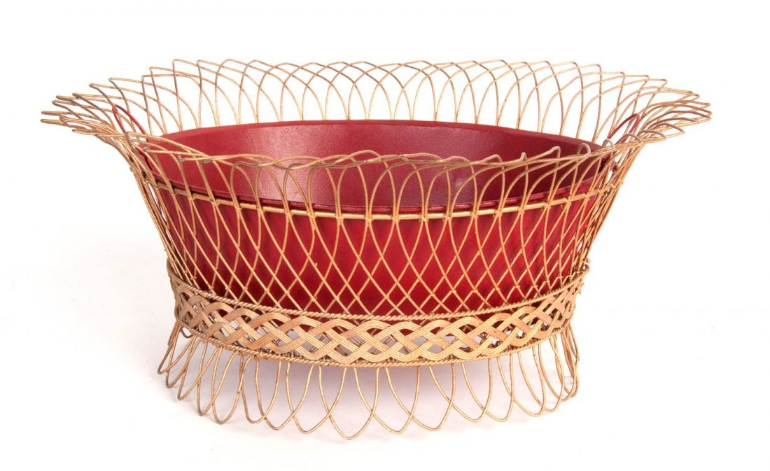 A red and gilt painted oval wirework jardiniere,