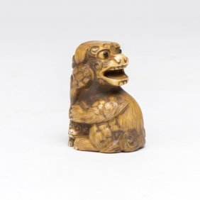 An Ivory Netsuke Of A Seated Karashishi With Young And
