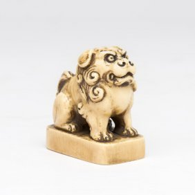 An Ivory Netsuke In The Form Of A Seal, With A Seated