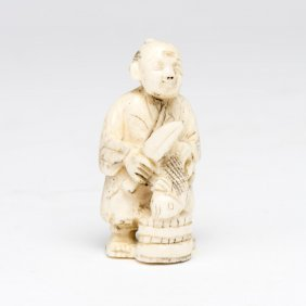 An Ivory Netsuke Of A Man Scaling A Fish, 20th Century