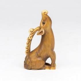 An Ivory Netsuke Of A Seated Deer, Howling At The Moon