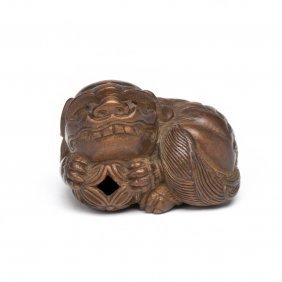 A Wooden Netsuke Crouching Karashishi Holding A Pieced