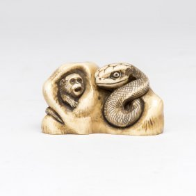 An Ivory Netsuke Of A Snake Pursuing Monkeys On A Rock,