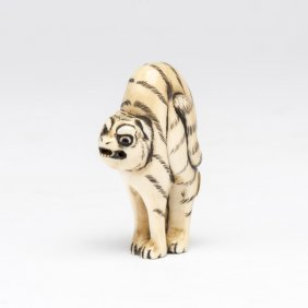 An Ivory Netsuke Of A Snarling Tiger With Arched Back