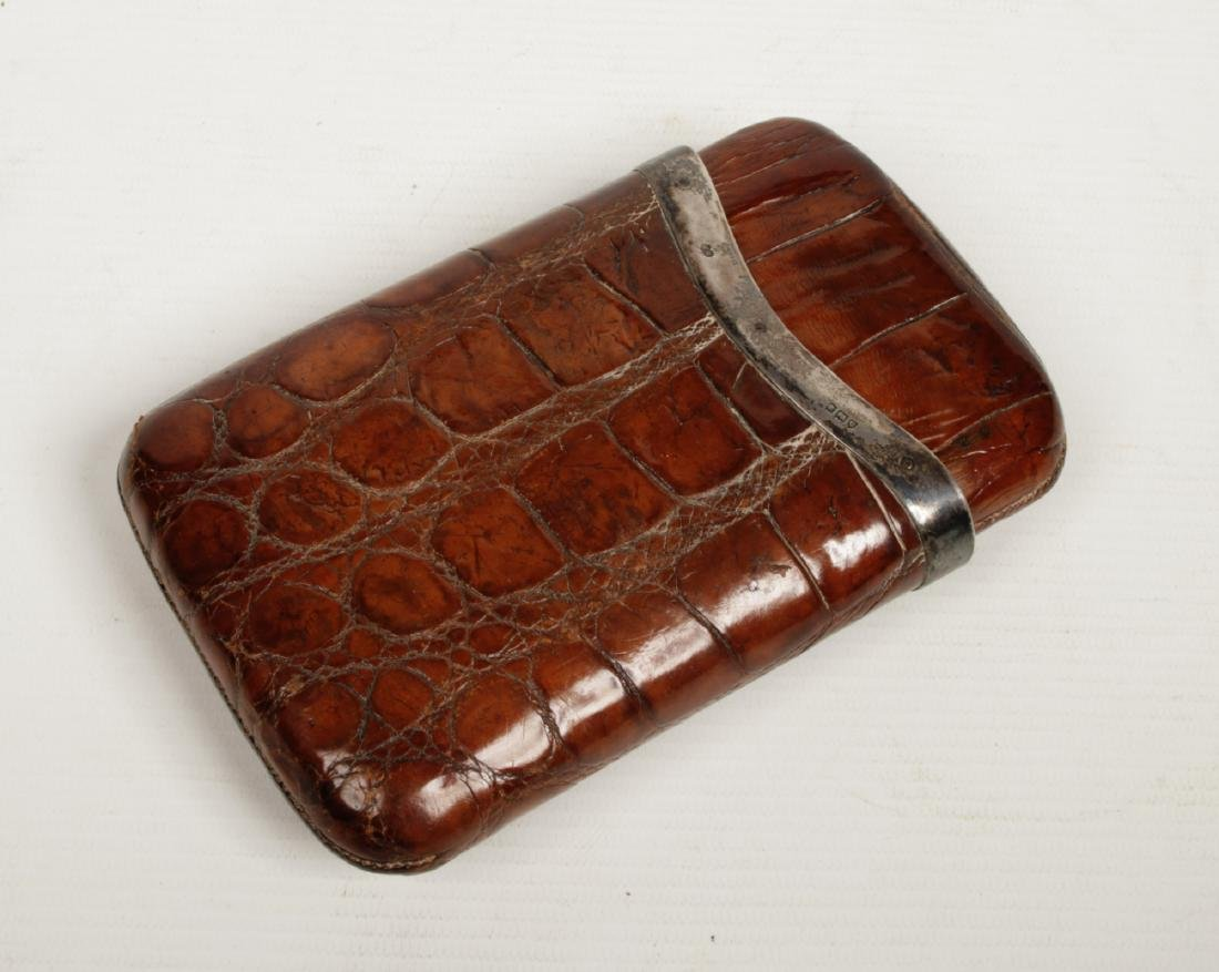 A crocodile skin cigar pouch with silver mount. Assayed