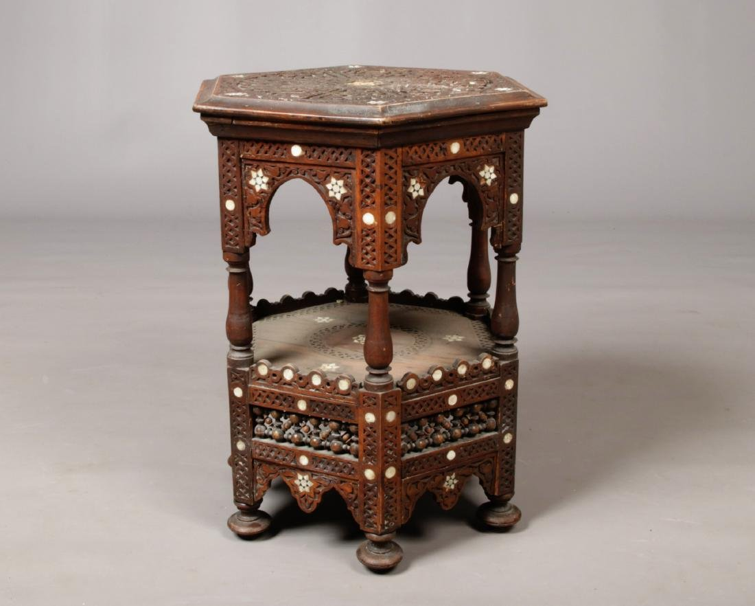 A middle eastern carved hexagonal two tier coffee table