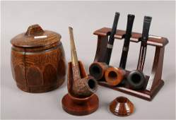 Four vintage pipes and two pipe racks, along with an