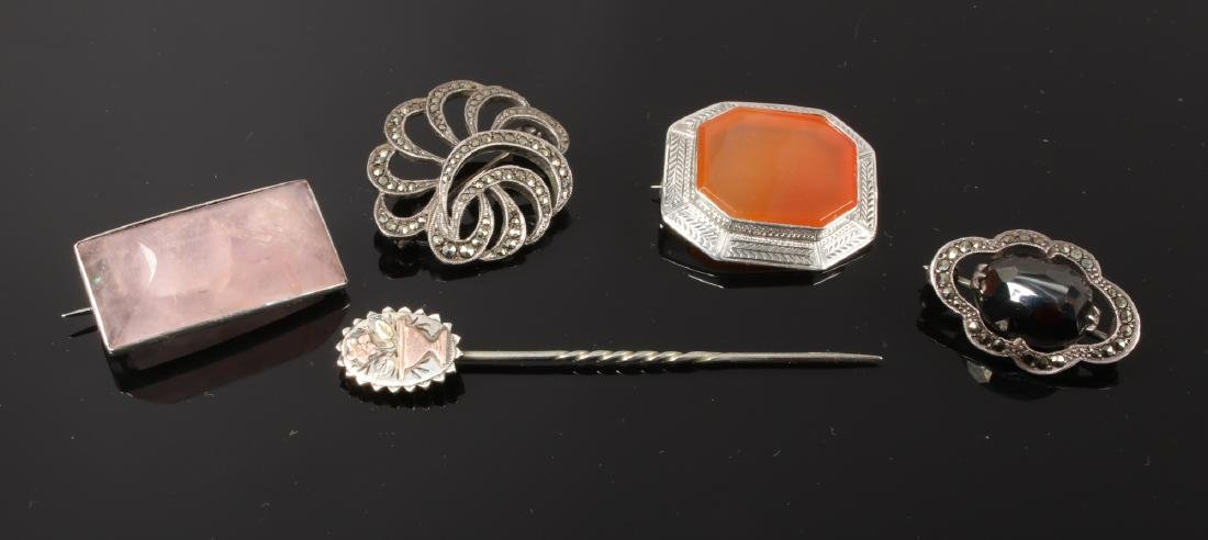 A gold applied stick pin and four silver brooches