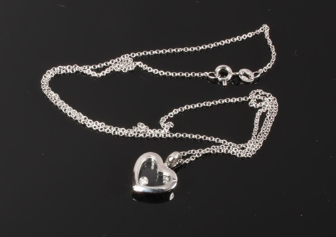 A 9ct white gold heart shaped pendant with floating