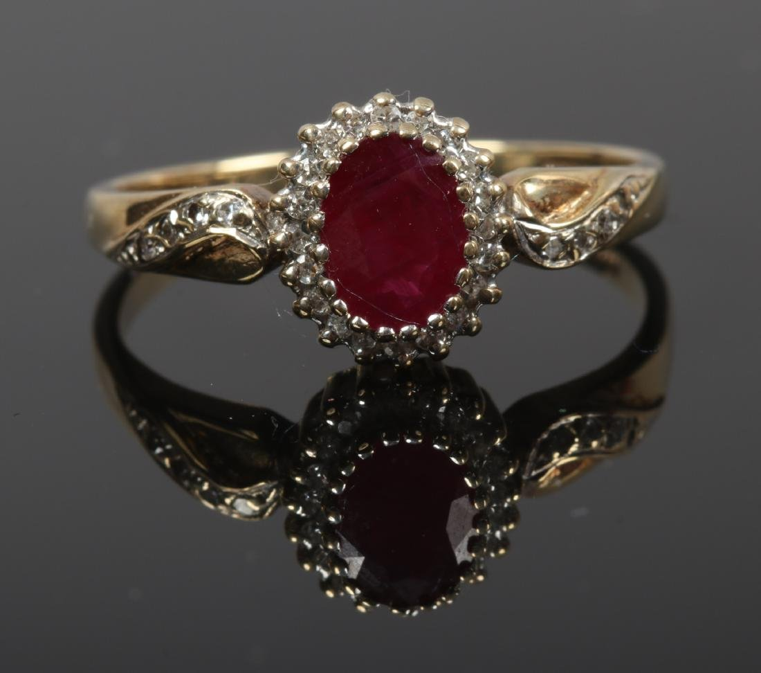 A 9ct gold halo cluster ring set with a ruby under a