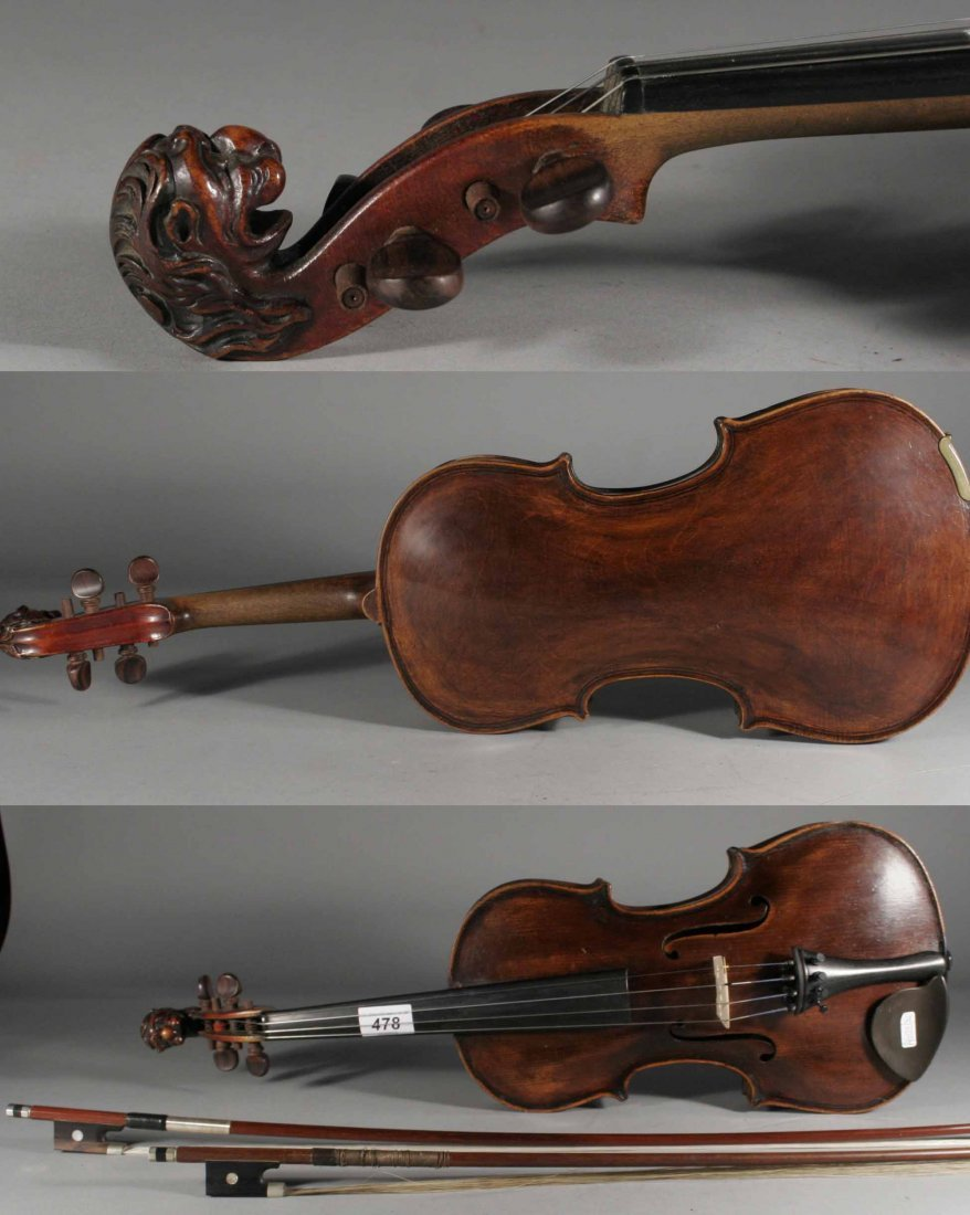 478: A cased violin and two bows with carved scroll for