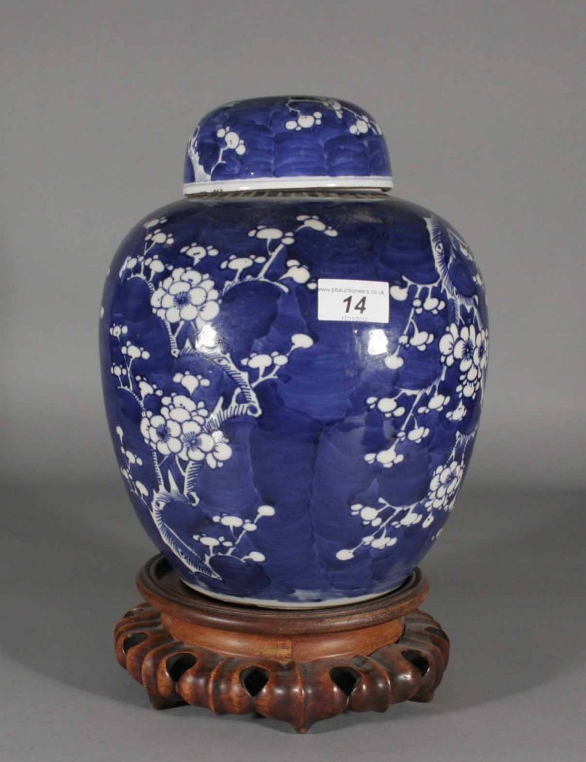 14: An antique Chinese ginger jar and cover on carved h