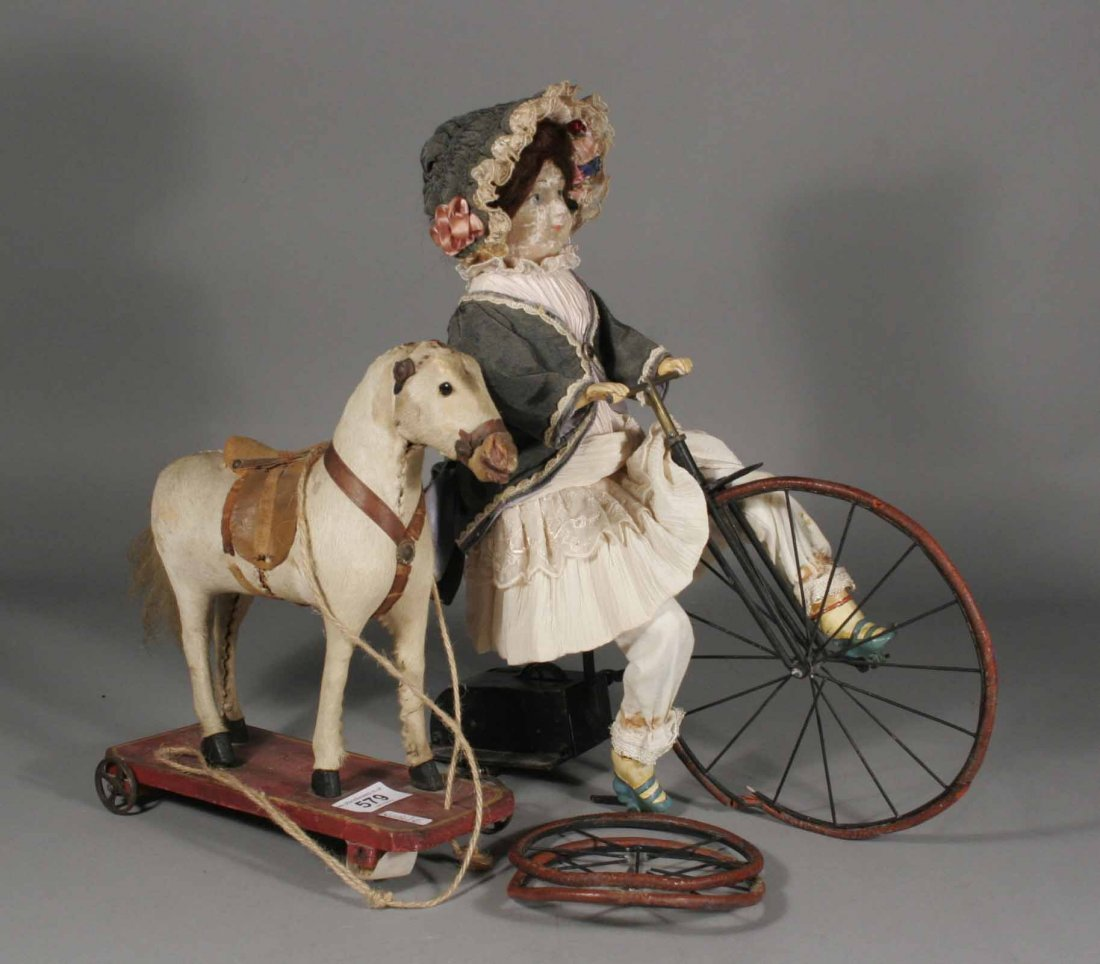 579: An Edwardian clockwork doll tricycle along with an