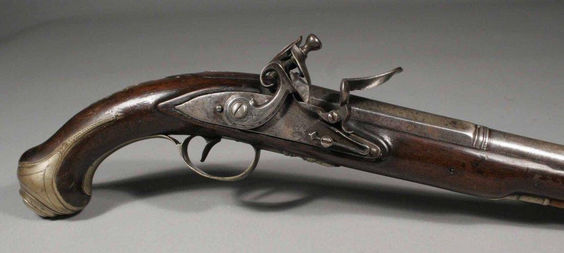 674: A Georgian flintlock pistol with carved walnut ful