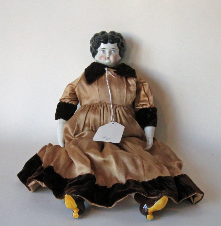 Brunette china-headed doll 19 inches long. Condition: