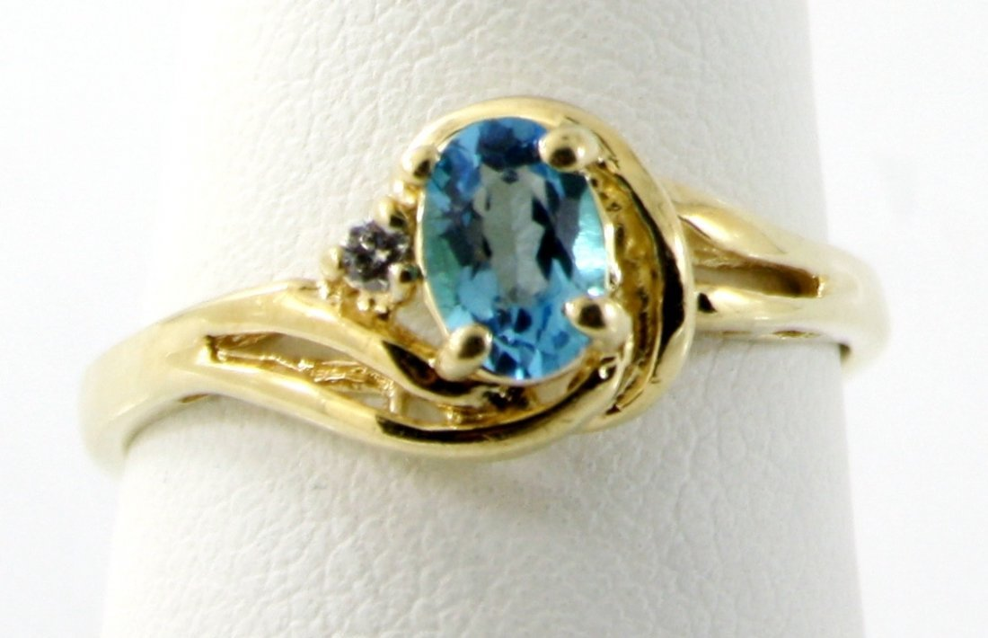 19: 10KT GOLD .50 CTW OVAL BLUE TOPAZ AND DIAMOND RING