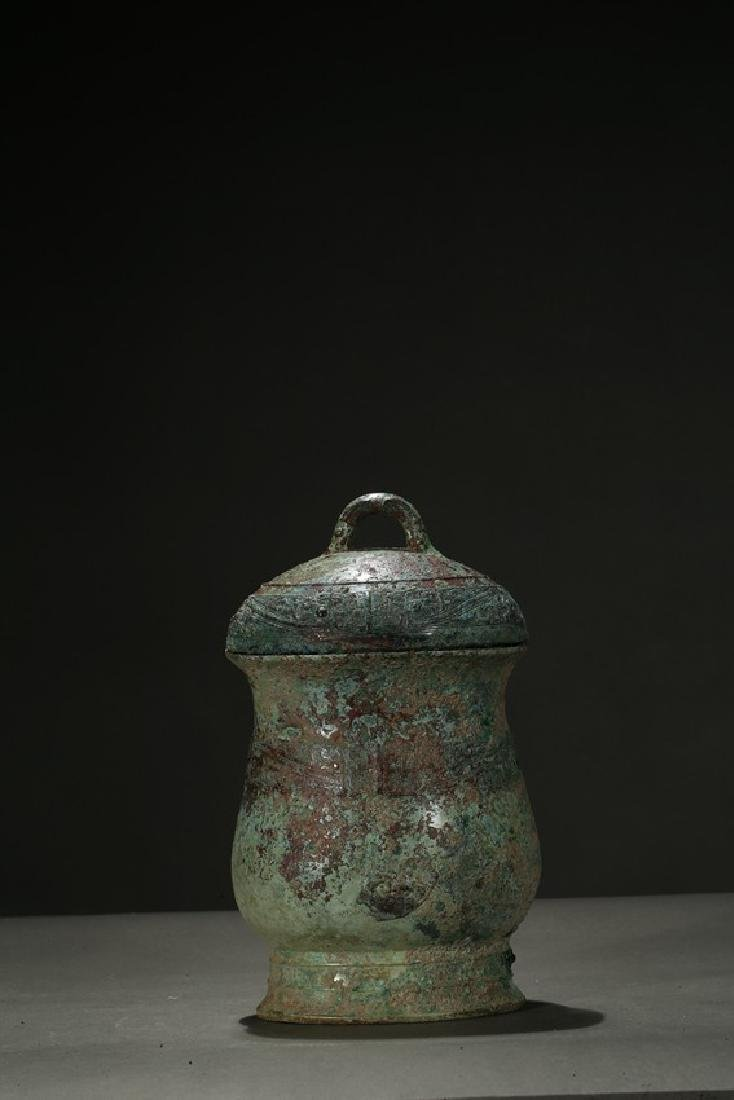 A BRONZE 'TAOTIE' WINE VESSEL AND COVER