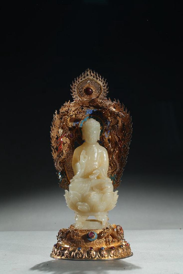 A WHITE JADE BUDDHA WITH GILT FILIGREE STAND