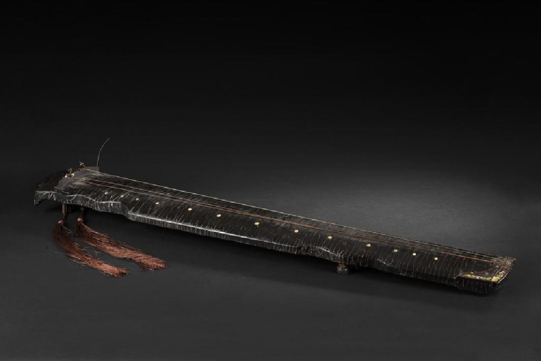 A LACQUERED WOOD GUQIN WITH INSCRIPTIONS