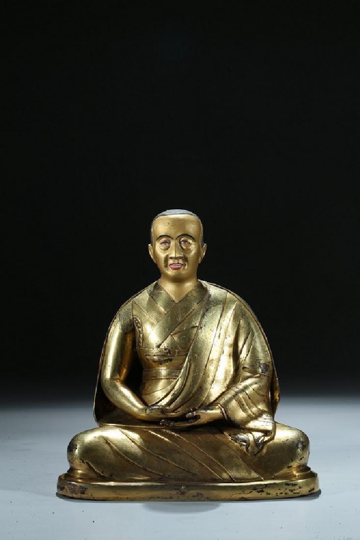 A GILT BRONZE FIGURE OF LAMA WITH INSCRIPTION