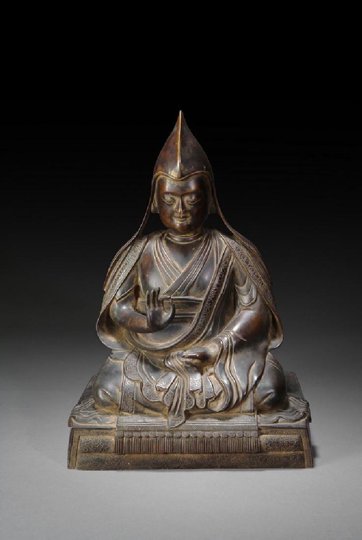 A BRONZE FIGURE OF SEATED LAMA