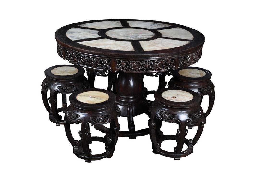 A SET OF ROSEWOOD CIRCULAR TABLE AND STOOLS INSET WITH