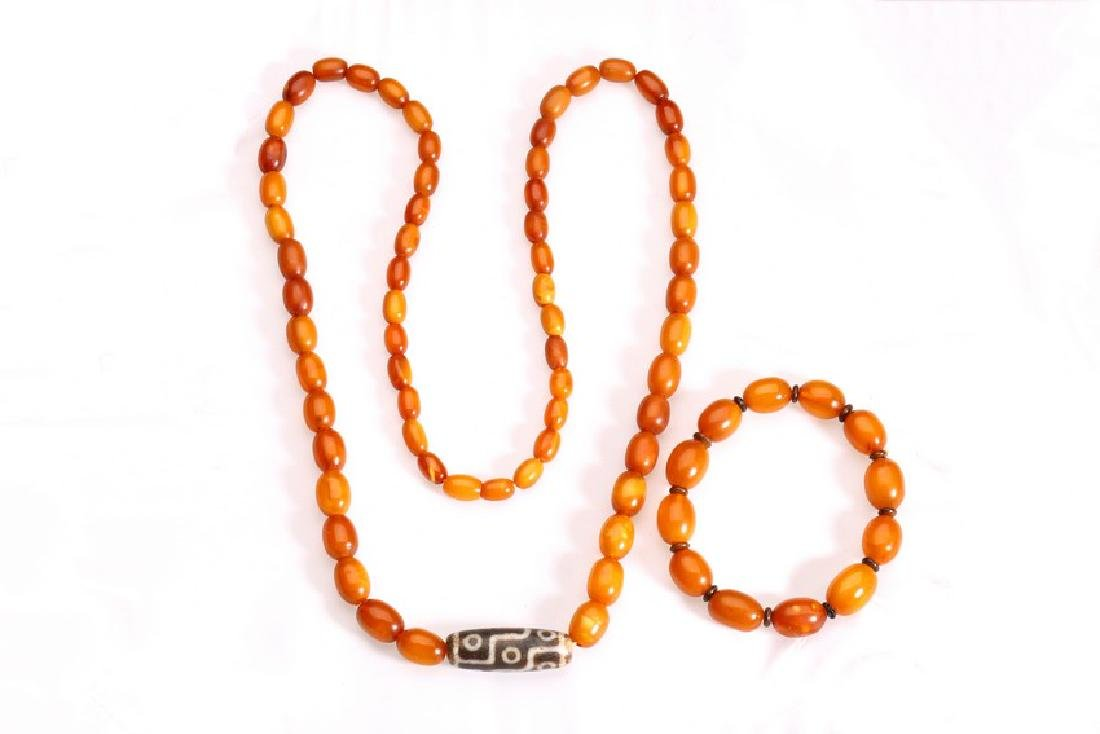 A GROUP OF TWO AMBER DZI NECKLACE AND BRACELET