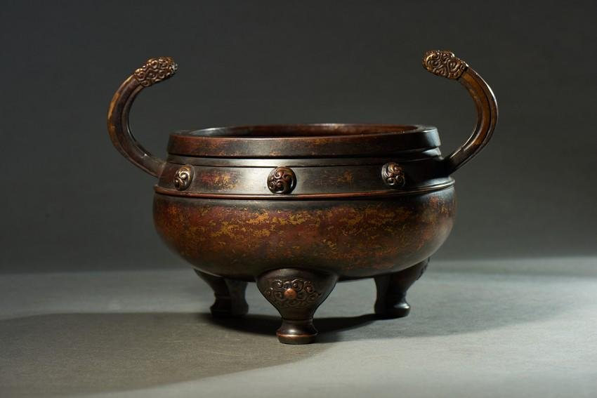 A BRONZE TWO-HANDLED TRIPOD CENSER