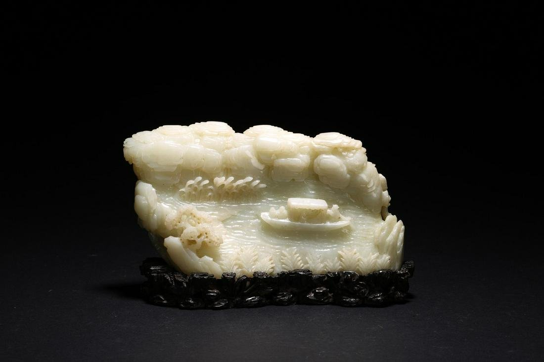 A CHINESE WHITE JADE BOULDER WITH STAND