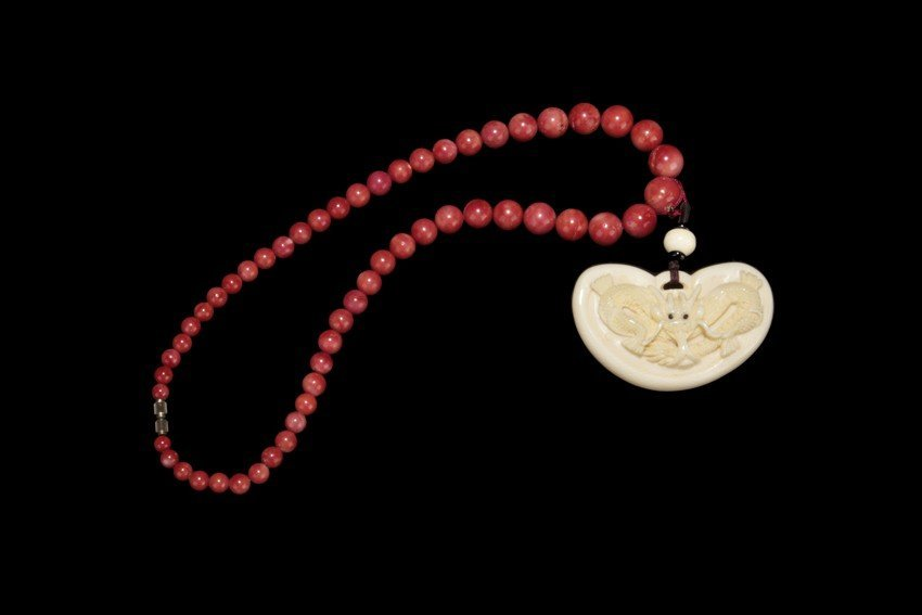 A strand of coral bead necklace with ivory pendant