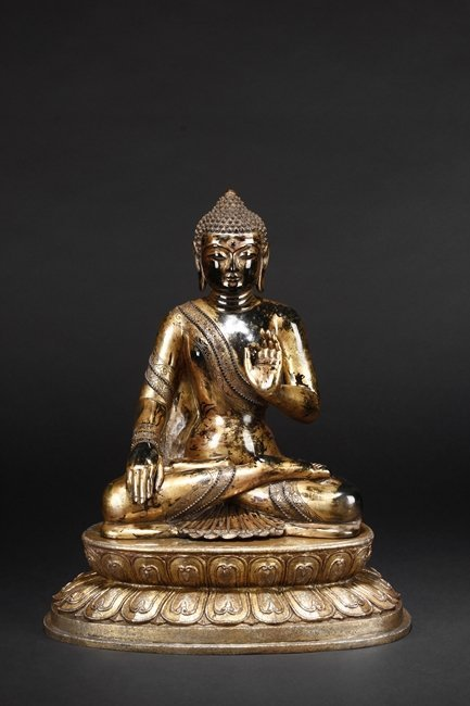 A CARVED BLACK JADE GILDED FIGURE OF SHAKYAMUNI