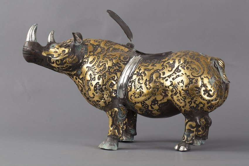 A GILT PAINTED BRONZE RHINOCEROS FIGURE