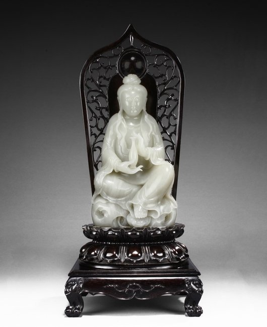 A LARGE WHITE JADE 'GUANYIN' WITH ZITAN BASE