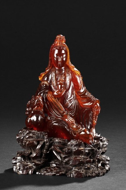 A VERY RARE CARVED AMBER FIGURE OF GUANYIN